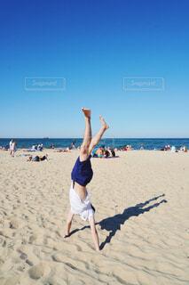 ビーチで逆立ちする男性の写真・画像素材[4543270]