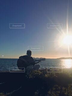 夕日とギター弾きの写真・画像素材[4432713]