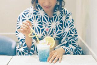 コーヒーを飲みながらテーブルに座っている女性の写真・画像素材[4579370]
