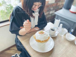 食べ物を食べるテーブルに座っている女性の写真・画像素材[4740525]