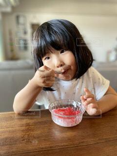 食べ物を食べるテーブルに座っている小さな女の子の写真・画像素材[4748519]