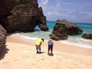 岩の多いビーチに立つ人々 のグループの写真・画像素材[1356205]