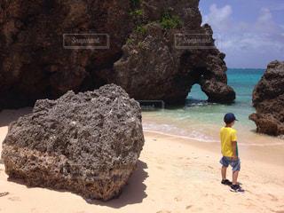 岩のビーチに立っている人の写真・画像素材[1406275]