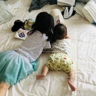寝転びながら絵本を読む姉と弟の写真・画像素材[4631300]