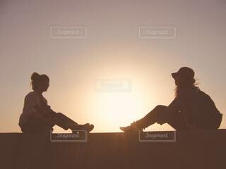 夕暮れに向かい合って座る2人の女性の写真・画像素材[4466485]