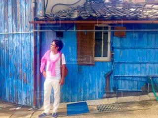 青色の建物の前に立つ男性の写真・画像素材[4467869]