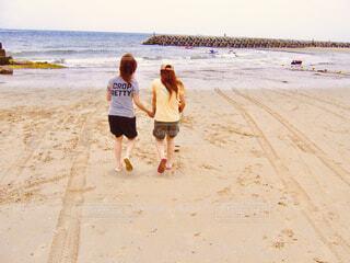 砂浜を海に向かって走る2人の女性の写真・画像素材[4467882]
