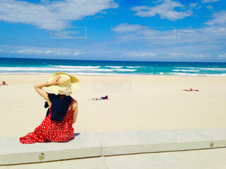 海辺で座る赤いワンピースの女性の写真・画像素材[4467891]