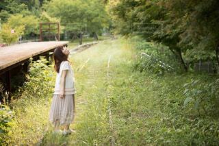 緑が生い茂る線路に立つ女性の写真・画像素材[4468183]