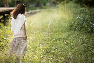 緑が生い茂る廃線に立つ後ろ姿の女性の写真・画像素材[4468184]