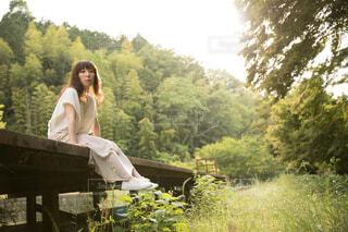 背後に山が見えるプラットホームに座る女性の写真・画像素材[4468191]