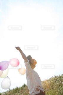 風になびく風船の束を持つ女性の写真・画像素材[4468189]