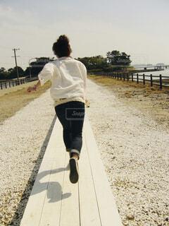 海辺の白い道を走る女性の後ろ姿の写真・画像素材[4468193]