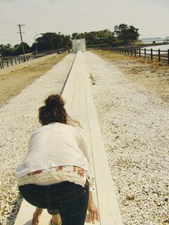 海辺の白い道で走る構えをする女性の写真・画像素材[4468194]