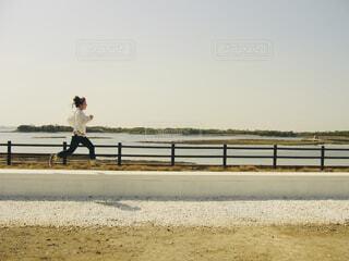 海沿いの道を走る女性の写真・画像素材[4468282]