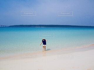 エメラルドグリーンの海に足をつける女性の写真・画像素材[4468485]
