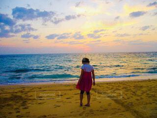 夕暮れの海に立つ女性の写真・画像素材[4468486]