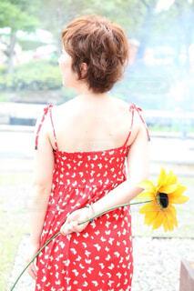 ひまわりのモチーフを片手で持って立つ女性の写真・画像素材[4468583]