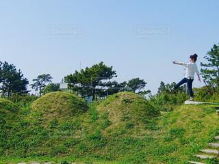 こぶのある丘を歩く女性の写真・画像素材[4468596]