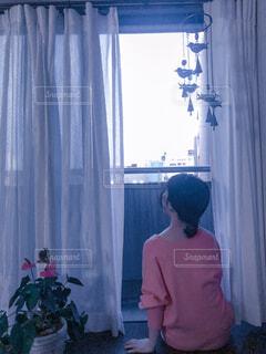窓辺に座る後ろ姿の女性の写真・画像素材[4560646]