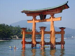 宮島の鳥居をくぐり抜けるカヌーの写真・画像素材[4460592]