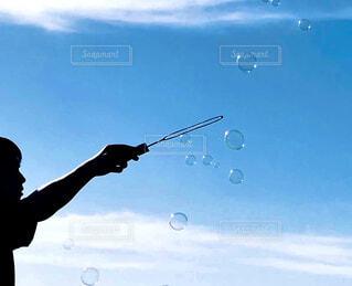少年と晴れた空にシャボン玉の写真・画像素材[4504448]