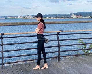 水の体の隣の桟橋の前に立っている女性の写真・画像素材[4588549]