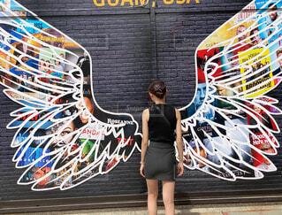 落書きで覆われた壁の前に立っている女性の写真・画像素材[4588776]