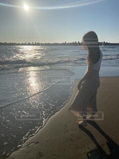 水の体の隣に立っている男の写真・画像素材[4588746]