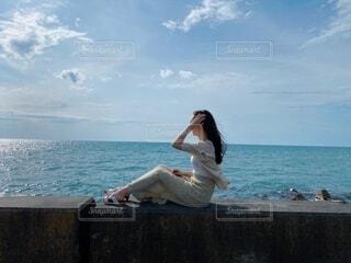 水の体の隣に座っている人の写真・画像素材[4653030]