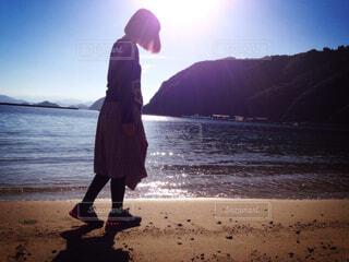青空の下砂浜を歩く女性の写真・画像素材[4510309]