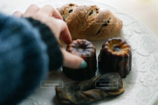 お皿の上のパンやカヌレを掴む手の写真・画像素材[4516841]