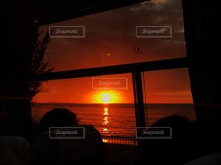 背景の夕日と暗い部屋で人の写真・画像素材[899871]