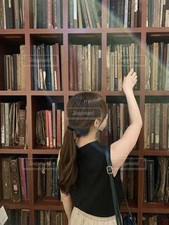 本棚の前に立っている女性の写真・画像素材[4500718]