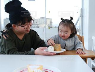 食事のテーブルに座っている姉妹の写真・画像素材[1021537]