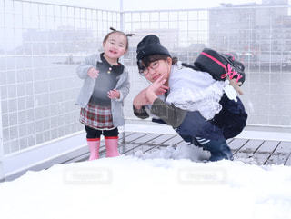 雪降る中で遊ぶ二人の写真・画像素材[1027490]