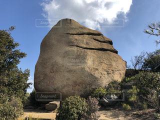 大きな岩の前で石像の写真・画像素材[1020394]