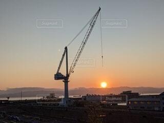 夕陽を吊ろうとしてる造船所のクレーンの写真・画像素材[4536302]