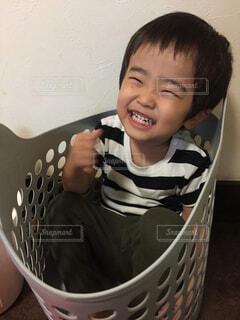 3歳男児が洗濯かごに収まって大満足しているところの写真・画像素材[4604487]
