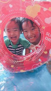 浮き輪から覗く姉弟の写真・画像素材[4604486]