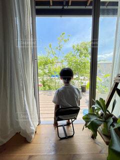 窓際で庭を眺める男の子の写真・画像素材[4604724]