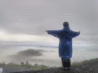 曇った青い空の前に立っている男の写真・画像素材[4495591]