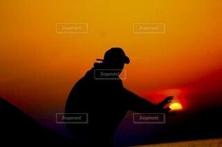 夕日の前に立っている男の写真・画像素材[4630628]