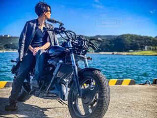 晴れの日に港でカスタムのバイクに乗る人の写真・画像素材[4557293]