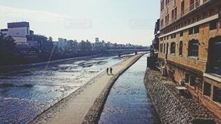 鴨川を走る自転車の2人(フィルム調)の写真・画像素材[4694925]