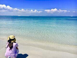水の体の近くのビーチに立っている女性の写真・画像素材[4698716]