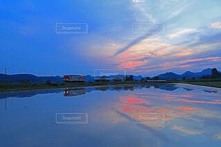 ローカル線に沈む夕陽の水鏡の写真・画像素材[4545508]
