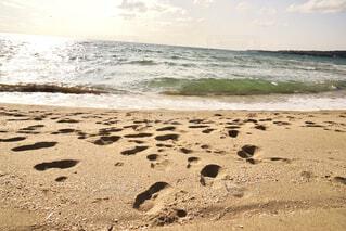 足跡のある砂浜に波が打ち寄せるの写真・画像素材[4613500]