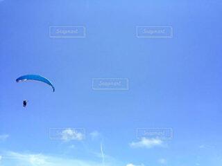青空と青いパラグライダーの写真・画像素材[4553636]