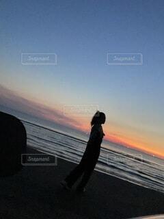 波打ち際を歩く女性の写真・画像素材[4660067]
